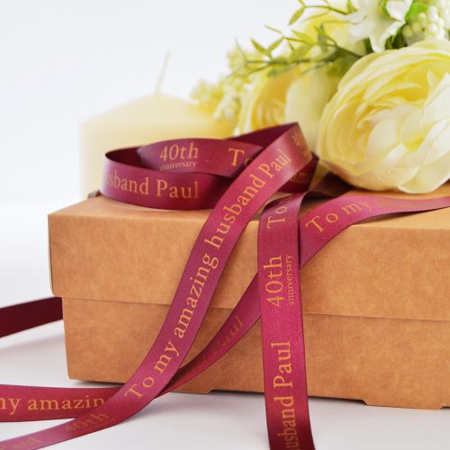 15mm personalised anniversary ribbon in burgundy with matt antique gold print