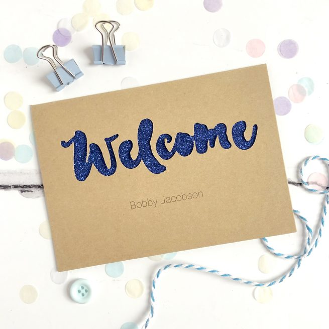 Personalised Welcome New Baby Glitter Cut Out Card in Kraft and Blue Glitter